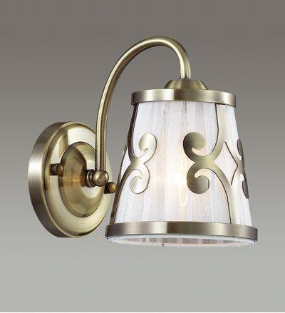 Настенный светильник бра Lumion 3285/1W FETIDAСовременные<br>Бра 3127/1W серии Fetida оформлена в классическом стиле. Светильник состоит из абажура из органзы, украшенного изящным металлическим декором и классической арматуры бронзового цвета. Классика формы и цвета позволит данной модели стать украшением любой комнаты.  Цоколь E14. Мощность 1х60W.  Нет ламп в комплекте.<br><br>Крепление: Настенное<br>Тип лампы: накаливания / энергосбережения / LED-светодиодная<br>Тип цоколя: E14<br>Количество ламп: 1<br>MAX мощность ламп, Вт: 60<br>Цвет арматуры: бронзовый
