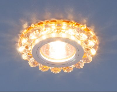 6036 MR16 GD золото Электростандарт Точечный светодиодный светильник с хрусталемВстраиваемые хрустальные светильники<br>Точечные светильники Elektrostandard™ предназначены для жилых и общественных помещений. Светильник подходит для всех типов подвесных потолков: гипсокартонных, натяжных и реечных. Cветильники оснащены светодиодной подсветкой, которая может быть включена как совместно с лампой, так и отдельно. Мягкий свет от светодиодов создает идеальную атмосферу для отдыха или просмотра телевизора.<br> Лампа: MR16 G5.3 max 50 Вт + LED Мощность LED подсветки: 3 Вт Диаметр: ? 90 мм Высота внутренней части: ? 20 мм Высота внешней части: ? 15 мм Монтажное отверстие: ? 70 мм Гарантия: 2 года<br><br>Тип цоколя: gu5.3<br>Диаметр, мм мм: 90<br>Диаметр врезного отверстия, мм: 70<br>Высота, мм: 15<br>MAX мощность ламп, Вт: 50