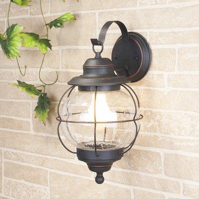 Regul D черная медь (арт. GLXT-1475D) Электростандарт Настенный светильникУличные настенные светильники<br>Цвет: черная медь Мощность: 1 x 60 Вт Цоколь: Е27 Питание: 220-240 В / 50 Гц Пылевлагозащита: IP44 Размер: 220 x 225 x 405 мм<br>Настенный светильник предназначен не только для внутреннего использования, но и для освещения садово-парковых зон вокруг дома, так как высокая степень пылевлагозащищенности позволяет использовать его под открытым небом.<br>Корпус светильника изготовлен из сплава алюминия с кремнием, что делает его легким и прочным, устойчивым к механическим воздействиям. Специальная порошковая окраска корпуса, наносимая в несколько слоев, позволяет добиться эффекта состаренного металла.<br>Для плафона использовано стекло, изготовленное вручную по технологии pulegoso. Пузырьки воздуха внутри стекла придают светильнику особое, неповторимое, очарование!<br>