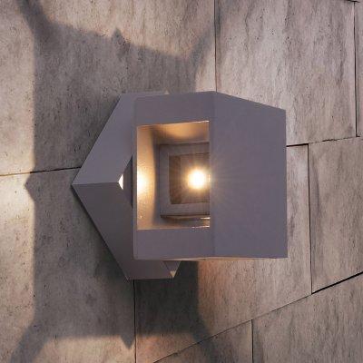 1606 Techno LED Tellus графит Электростандарт Настенный светильникУличные настенные светильники<br>Мощность: 12 Вт Световой поток: 1020 лм Свет: 4200 К белый Источник света: 4 светодиода Срок службы светодиодов: 50 000 ч Пылевлагозащищенность: IP65 Питание: 170 - 240 В, 50 Гц Рабочая температура: -20° ... +40° С Материал корпуса: Алюминиевый сплав Размеры: 100 х 100 х 94 мм Гарантия: 3 года <br>Светильник оснащен поворотным механизмом.<br>